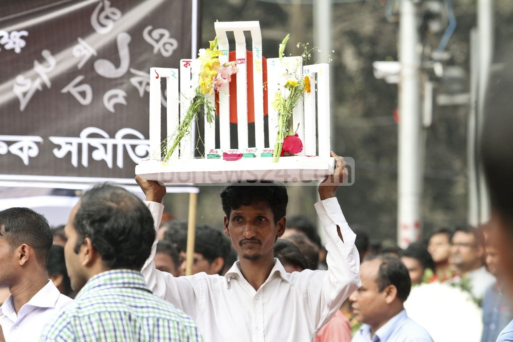 A man carries a model of the Central Shaheed Minar to pay tribute to the Language martyrs on Tuesday. Photo: tanvir ahammed