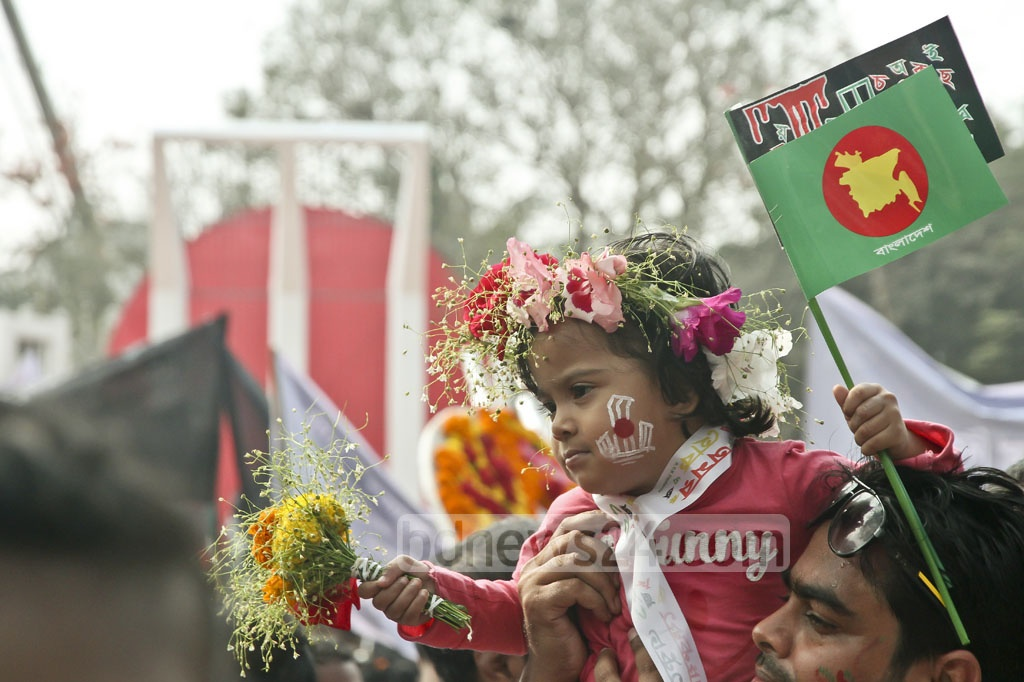 Children carry bouquets of flowers at the Central Shaheed Minar to commemorate the Language martyrs of 1952 on Tuesday. Photo: tanvir ahammed