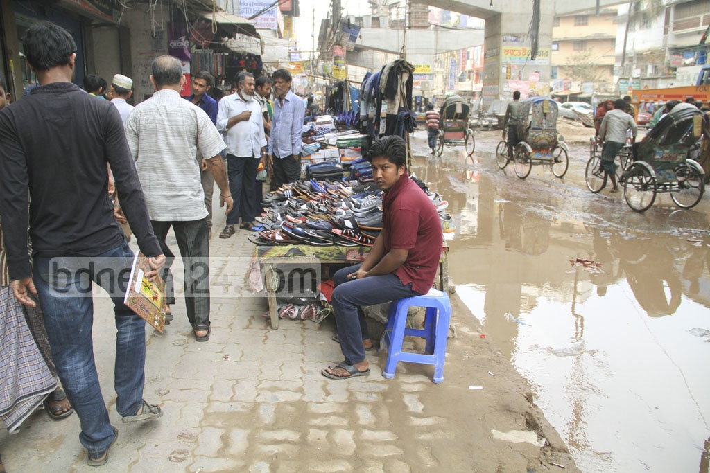 Water on the road and hawkers on the footpath leave pedestrians at sea.