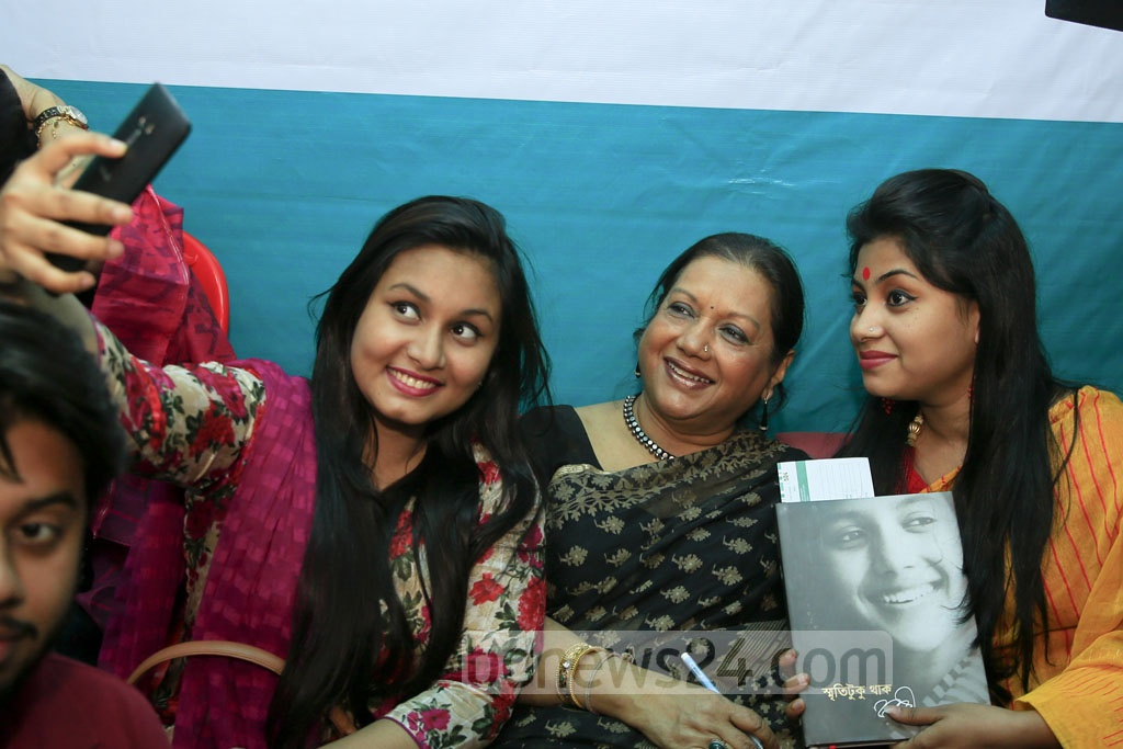 Sarah Begum Kabori, known as the 'sweet damsel' of Bangla cinema, poses for selfie with her fans after the launching of her memoirs at the Ekushey Book Fair on Saturday. bpl, a sister concern of bdnews24.com, is the publisher of the book 'Smriti Tuku Thaak'.
