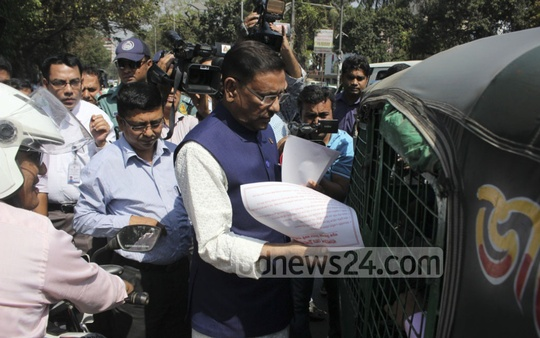 Road Transport and Bridges Minister Obaidul Quader distributes awareness leaflets to passengers during an inspection of the BRTA Mobile Court set up at Dhaka's Topkhana Road on Sunday. Photo: asif mahmud ove