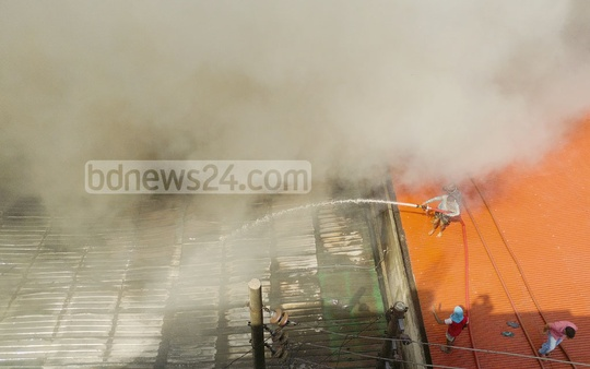 Local people extended their hands to the fire crews to douse the fire that broke out at a shoe factory at Jartabarhi on Monday. Photo: abdul mannan