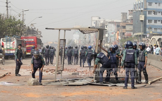 Police remove what remained of a police box, torched and dumped on the middle of the road by agitating transport workers at Gabtali. Photo: asif mahmud ove