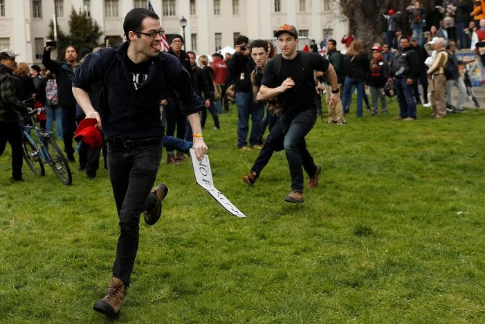 A counter-demonstrator in opposition of US President Donald Trump runs after taking a hat from a pro-Trump supporter during a 'People 4 Trump' rally in Berkeley, California March 4, 2017. REUTERS