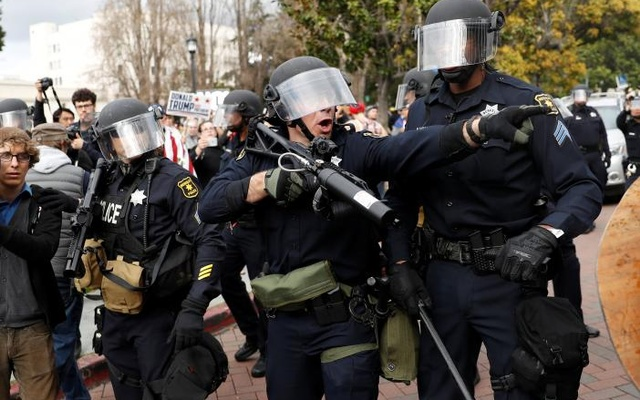 A police officer gestures as supporters of US President Donald Trump and counter-protesters scuffle during a 'People 4 Trump' rally in Berkeley, California March 4, 2017. REUTERS