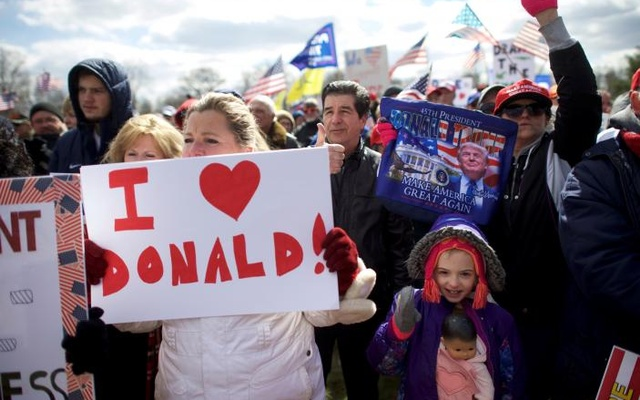 Gia Morris (R), 8, carries a doll while cheering during a 'People 4 Trump' rally at Neshaminy State Park in Bensalem, Pennsylvania, US March 4, 2017. REUTERS