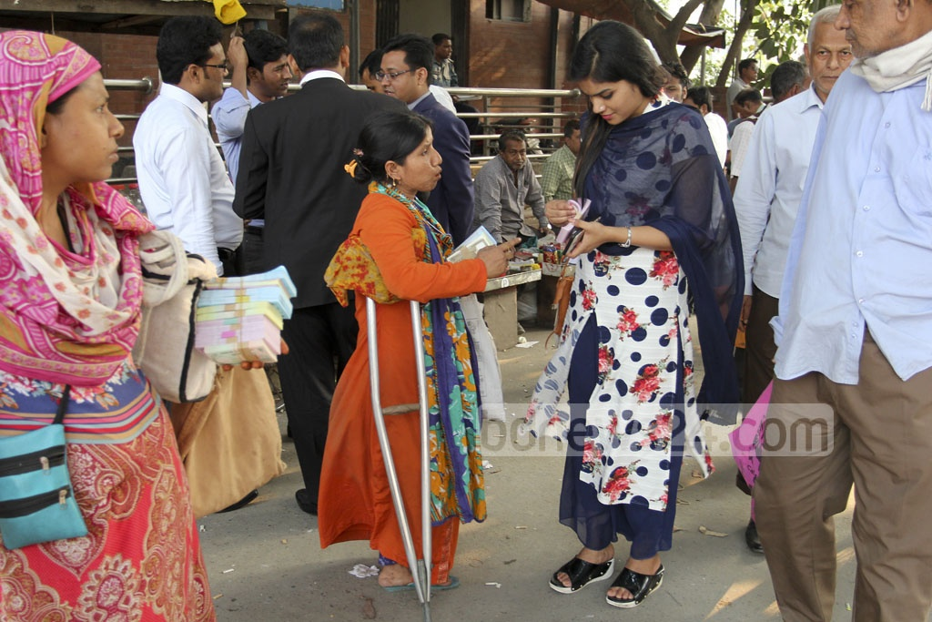Undeterred by physical handicap, Ayesha sells new currency notes to buyers. Photo: asif mahmud ove