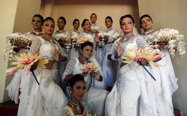 A group of female traditional dancers pose for photographs during the