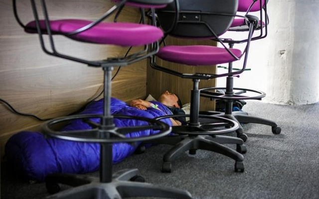 A participant sleeps under a desk during a weekend Hackathon event, in San Francisco, California, US Jul 17, 2016. Reuters