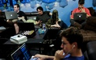 Zander Dejah (2nd L), 25, who works as a Virtual Reality engineer, Nick Olszowy (C), 25, a software engineer and Andrew Bresee, 26, a software engineer, all who are residents of The Negev tech house, use their electronics during a Sunday 'family' dinner in San Francisco, California, US Oct 30, 2016