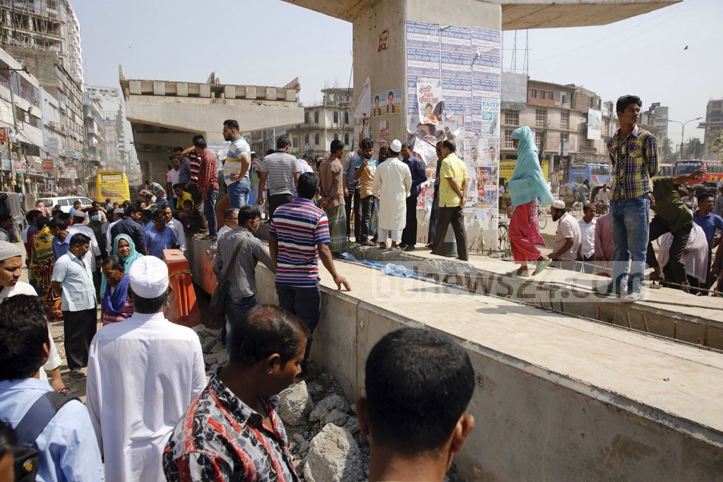 Onlookers throng the accident site where one person was killed and two others injured when a girder of an under-construction flyover collapsed near capital's Malibagh level-crossing at the early hours on Monday. Photo: mostafigur rahman