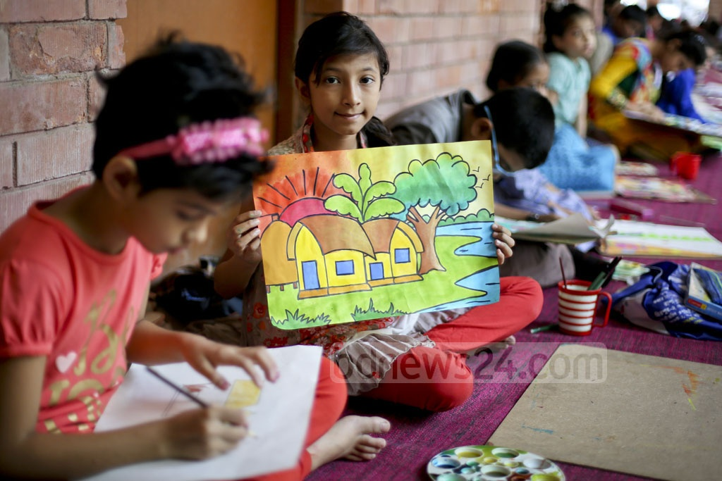 A girl shows her painting on Bangabandhu at a competition on his 97th birth anniversary and National Children Day on Friday. Photo: asaduzzaman pramanik