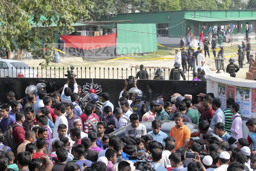 Reporters flock the entrance to the site in Dhaka's Ashkona where the RAB's new headquarter is being constructed. A man, believed to a suicide bomber, died in a blast after reportedly trying to climb over the wall.