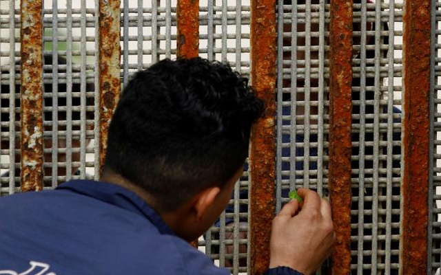 A man, who was deported from the US seven months ago, receives candy from his nephew across a fence separating Mexico and the United States as photographed from Tijuana, Mexico, Mar 4, 2017. Picture taken from the Mexican side of the border. Reuters