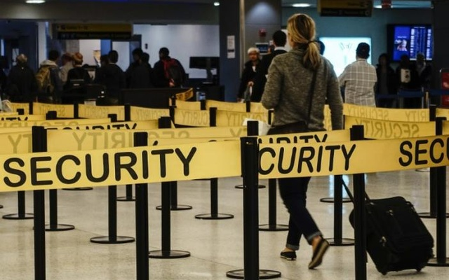 Passengers make their way in a security checkpoint at the International JFK airport in New York Oct 11, 2014. Reuters