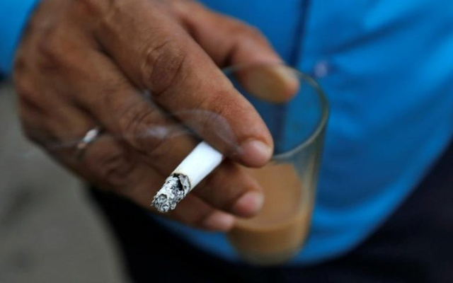 A man smokes a cigarette along a road in Mumbai, Oct 26, 2016. Reuters