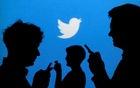 FILE PHOTO: People holding mobile phones are silhouetted against a backdrop projected with the Twitter logo in this illustration picture taken September 27, 2013. Reuters