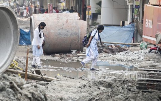 Pedestrians and students have to negotiate polluted water at Malibagh level-crossing. Photo: asif mahmud ove