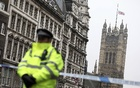 A police officer stands on duty as the union flag flies over Parliament at half-mast the morning after the attack by a man driving a car and weilding a knife left five people dead and dozens injured, in London, Britain, March 23, 2017. Reuters