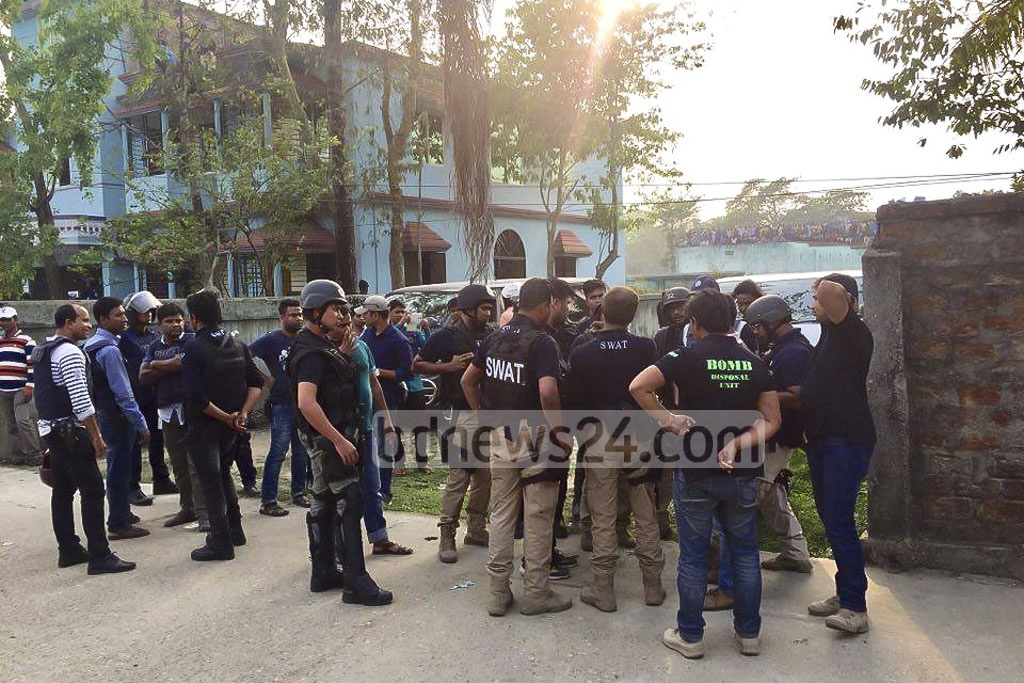 Members of a SWAT team and bomb-disposal team prepare outside a suspected militant hideout at Sylhet's South Surma.