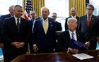 US President Donald Trump smiles after announcing a permit for TransCanada Corp's Keystone XL oil pipeline while TransCanada Chief Executive Officer Russell Girling (L), US Commerce Secretary Wilbur Ross (C) and Energy Secretary Rick Perry (R) stand beside him in the Oval Office of the White House in Washington, US, Mar 24, 2017. Reuters