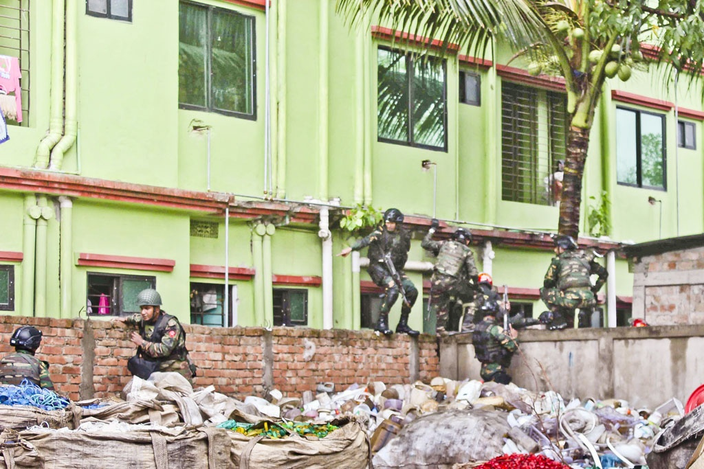 Commandos are seen climbing a wall behind the two buildings.Photo: ISPR