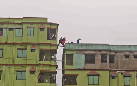 A commando helps a woman cross a ladder that was being used to bridge the rooftops of two buildings.Photo: ISPR