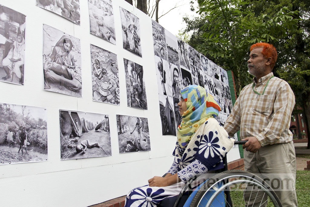 Visitors look at a photo exhibition in honour of Independence Day at the National Memorial on Sunday. Photo: asif mahmud ove