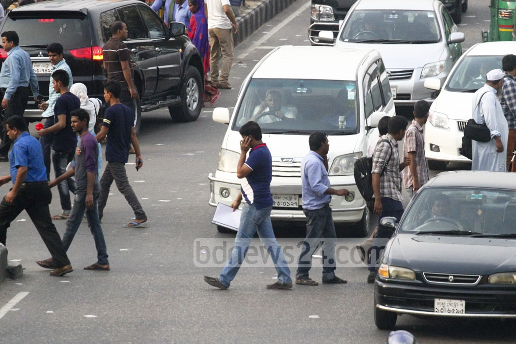 Jaywalking: A man using a mobile phone while crossing the street at Kakoli in the capital's Banani on Monday. Photo: abdul mannan