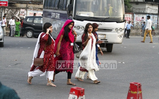 Jaywalking: Two of the four women even using mobile phones while crossing the street at Kakoli in the capital's Banani on Monday. Photo: abdul mannan