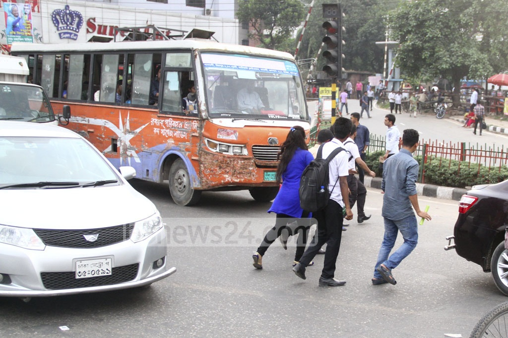 Jaywalking: School kids and parents flag down running vehicles to cross the busy Airport Road, though the footbridge is close by at Kakoli in the capital's Banani on Monday. Photo: abdul mannan