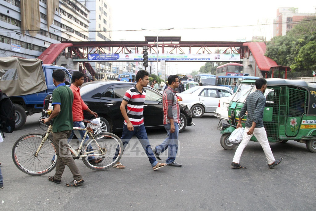 Jaywalking: Pedestrians risk their lives to cross the street at Kakoli in the capital's Banani on Monday. Photo: abdul mannan