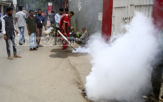 Amid growing mosquito menace, a city corporation worker is spraying insecticides at Banani's Chairmanbarhi in Dhaka on Monday. Photo: abdul mannan