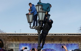 A law enforcement officer climbs on a lamp pole to detain opposition supporters during a rally in Moscow, Russia, Mar 26, 2017. Reuters