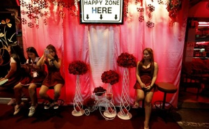Women sit outside a go-go dance bar in Pattaya, Thailand, March 25, 2017. Reuters