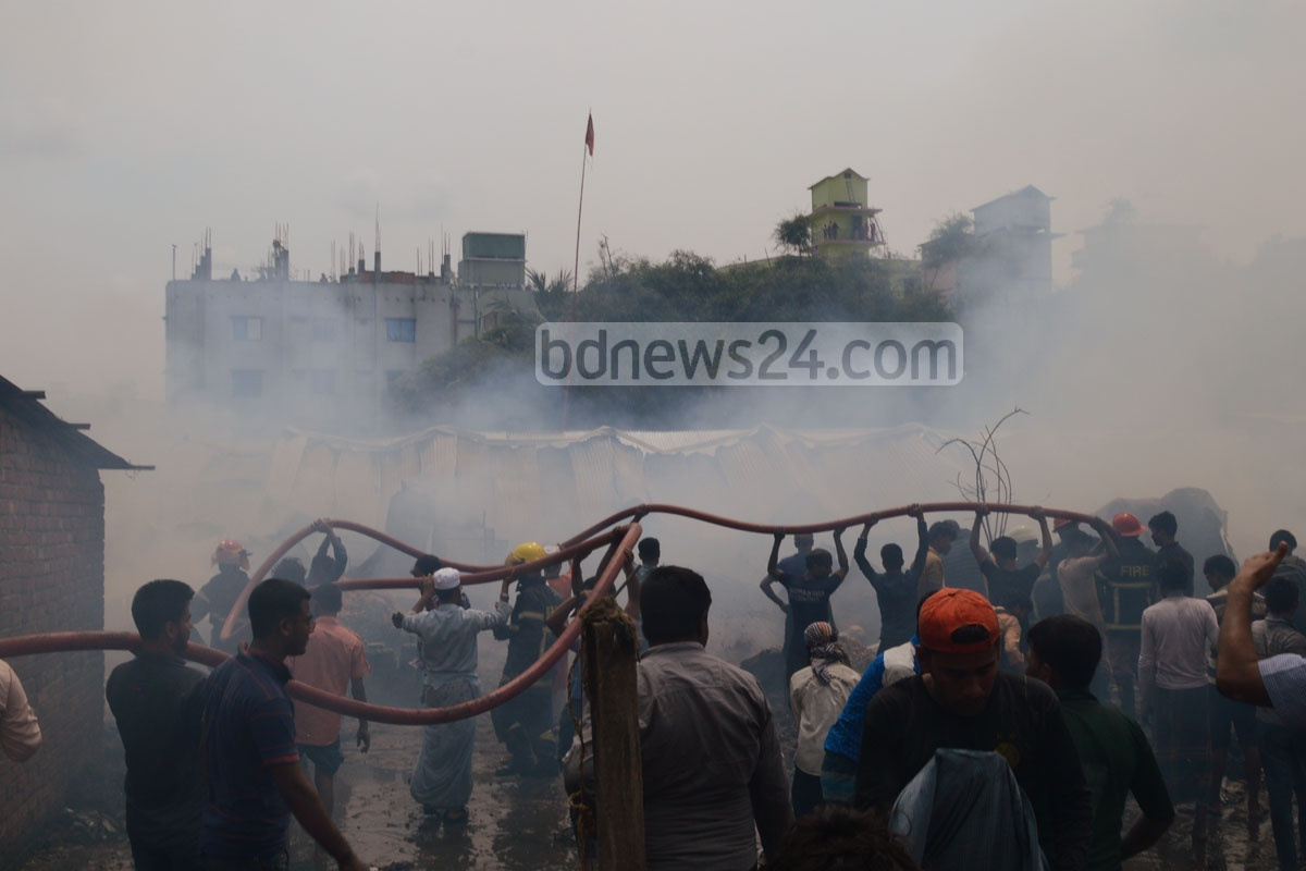 Locals at Chittagong's Muradpur join firefighters in their effort to douse a fire at a slum on Tuesday noon. Photo: suman babu