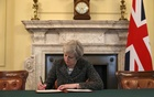British Prime Minister Theresa May in the cabinet, sitting below a painting of Britain's first Prime Minister Robert Walpole, signs the official letter to European Council President Donald Tusk invoking Article 50 and the United Kingdom's intention to leave the EU on Mar 28, 2017 in London, England. Reuters