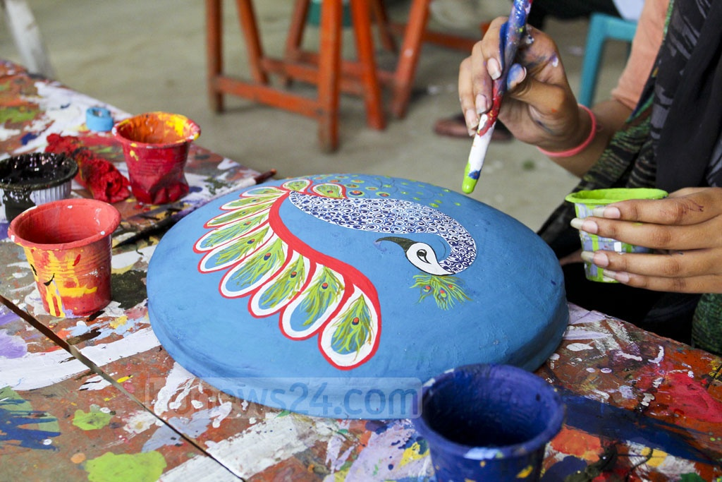 A student of Dhaka University's Faculty of Fine Arts is painting a clay pot in preparations of Pahela Baishakh celebrations, which is just two weeks away.