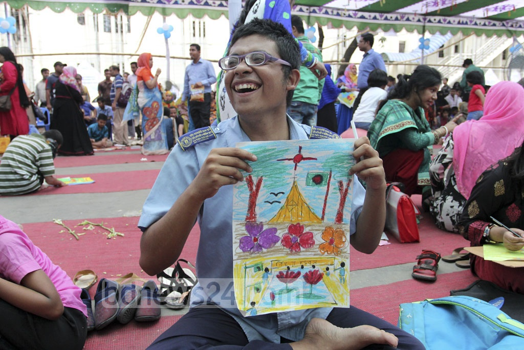 An autistic child shows his work at the art camp organised at the Bangabandhu Sheikh Mujib Medical University on the occasion of World Autism Awareness Day on Saturday. Photo: asif mahmud ove