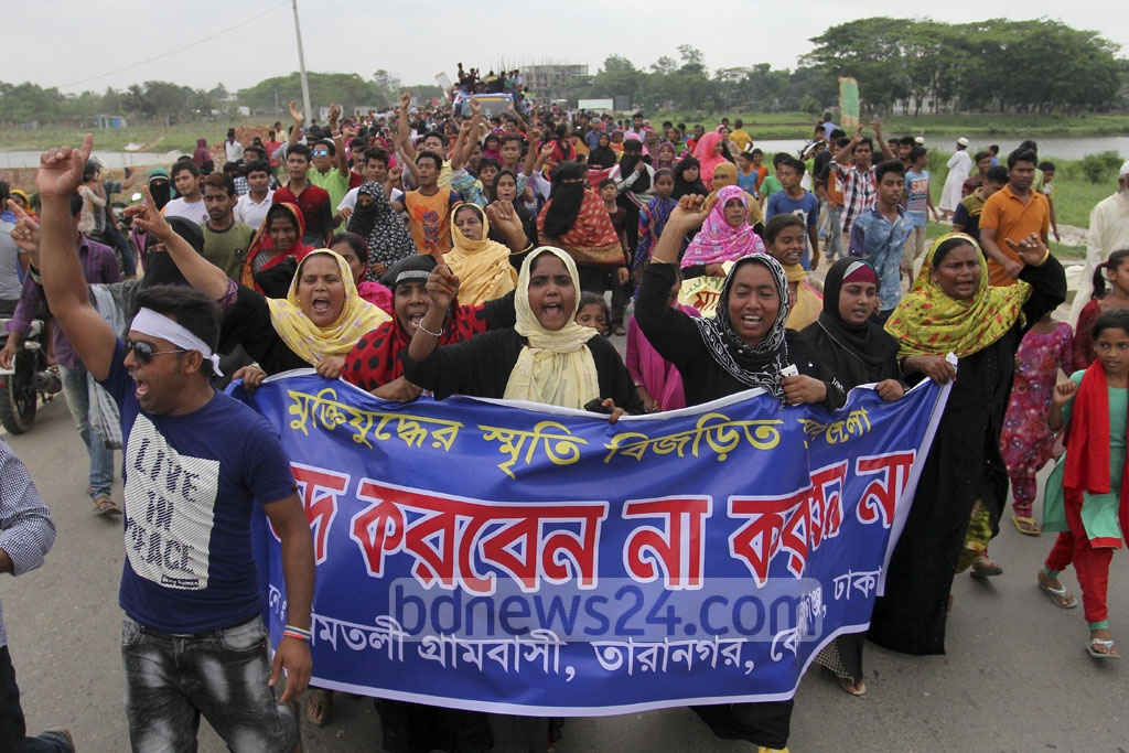 Residents of Keraniganj and Savar demonstrate on Kolatia-Mohammadpur road in Keraniganj against a RAJUK plan to build a model town by acquiring land on Monday. Photo: asif mahmud ove