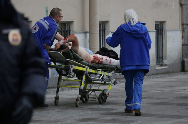 An injured person is helped by emergency services outside Sennaya Ploshchad metro station, following explosions in two train carriages at metro stations in St. Petersburg, Russia April 3, 2017. REUTERS
