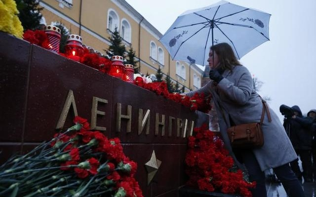 A woman lays flowers during a memorial service for victims of a blast in St.Petersburg metro, at a memorial by the Kremlin walls in Moscow, Russia April 3, 2017. REUTERS