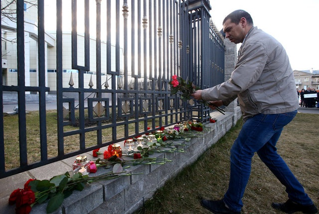 A man lays flowers to commemorate victims of a blast in Russian St.Petersburg metro, at the Russian embassy in Minsk, Belarus April 3, 2017. REUTERS