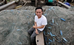Fisherman Peter Nguyen Van Hai sits between nets on his family's fishing boat at Con Se fishing village of Vietnam's central Quang Binh province Mar 31, 2017. Reuters