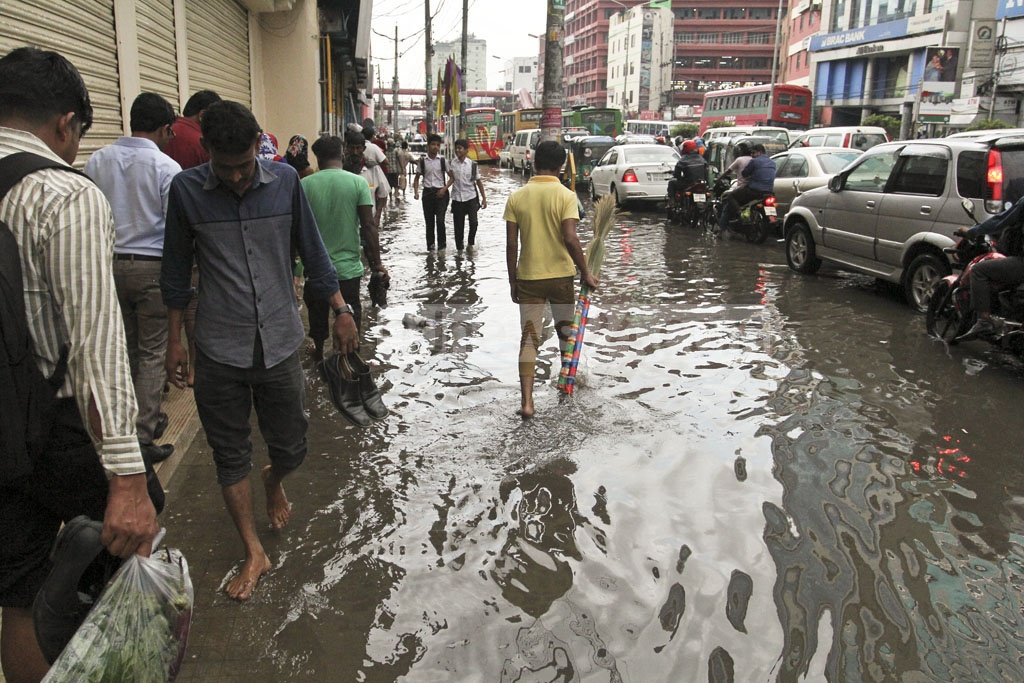 Commuters struggle to make their ways through a waterlogged road at Dhaka's Kazi Nazrul Islam Avenue. The road was submerged following an hour-long downpour on Wednesday. Photo: asif mahmud ove