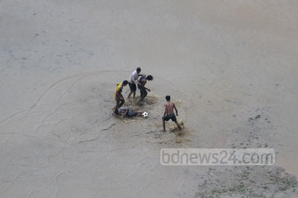 Youths play football on a near-submerged slippery playground at Titumir College in the capital after an untimely heavy downpour caused commuting havoc in the city on Wednesday. Photo: abdul mannan