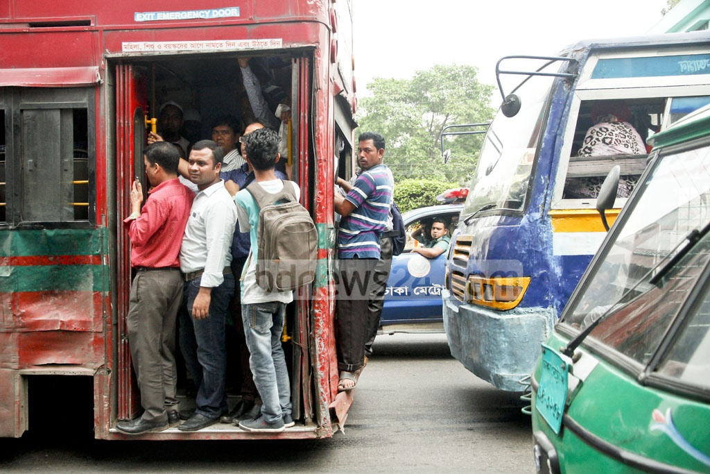 Commuters choose risky perches on Dhaka buses on Thursday rather than face long waits due to tight security measures for the Islamic Foundation Conference. Photo: tanvir ahammed