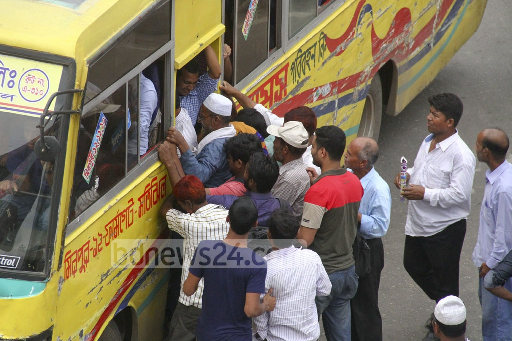 People rush to board one of the few buses operating in Dhaka on Thursday during the Islamic Foundation Conference. Photo: abdul mannan