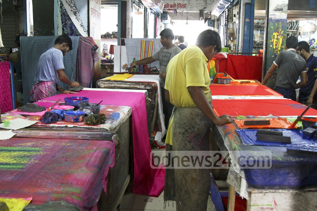 Boutique artists are seen busy working ahead of impending Pahela Baishakh or Bangla New Year when women prefer wearing locally made cotton sharees. This picture is taken from Dhaka's New Market area on Friday. Photo: abdul mannan
