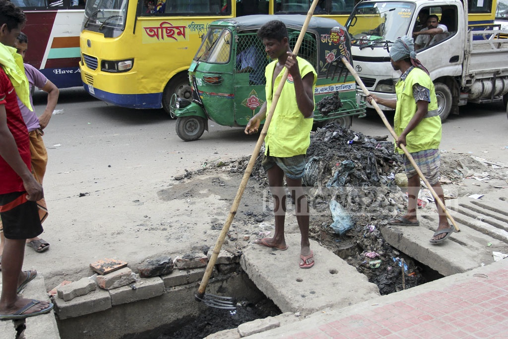 Sewage lines being cleaned in Dhaka's Pragati Sarani on Saturday. Photo: asif mahmud ove